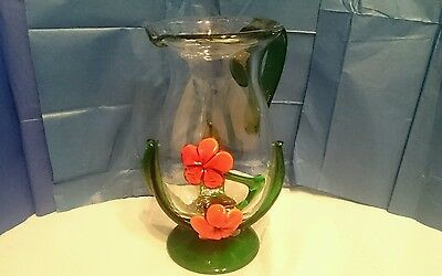 Unique hand blown glass art water pitcher with raised glass flowers and stems.