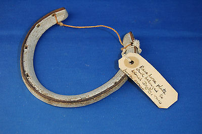 An antique metal horse shoe, horse racing plate, dated 1906, label attached