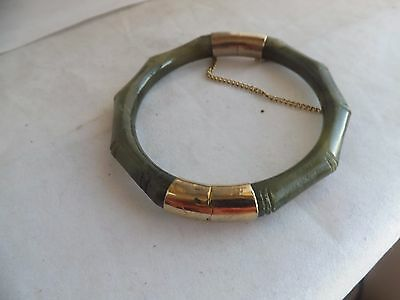 a vintage jade bangle with yellow metal fixings