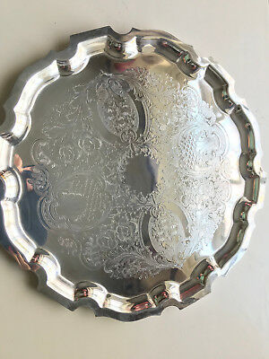 Silver plated serving tray with engraved patterns.