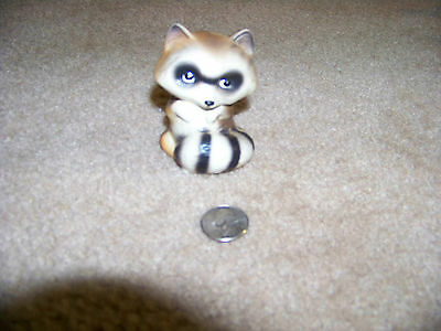 Porcelain sitting raccoon with tail wrapped around.  Stamped A354 on bottom