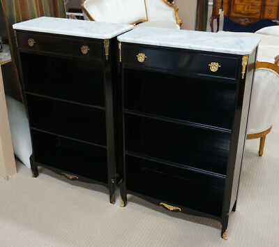 Pair of ebony bookcases with white marble tops and brass hardware