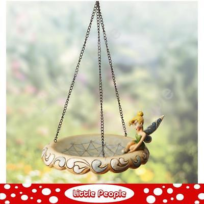 Tinker Bell, the adorable fairy, sits on the edge of this bird feeder