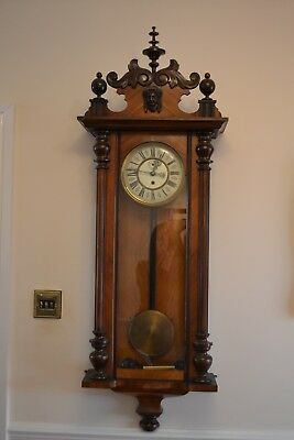 Vienna walnut wall clock with carved pediment, glass door and round dial