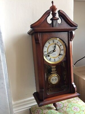 Victorian style reproduction wall clock with pendulum.
