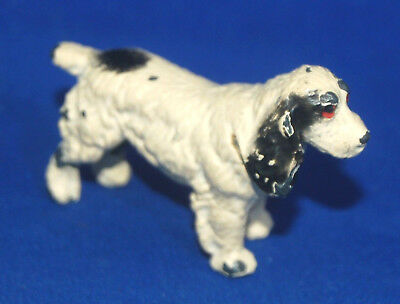 A lovely small antique painted cast metal standing spaniel dog figure