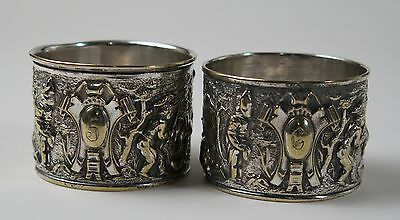 Pair of high relief cast silver plated napkin rings with bacchanalian scenes