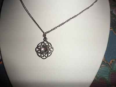 silver coloured metal Celtic pendant with chain and crystal stone in centre