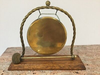 Antique brass and oak dinner gong in good condition.