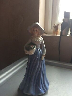 Unmarked Figurine of a lady in hat carrying a basket of flowers