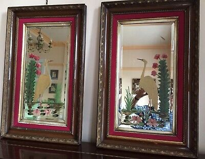 A pair of antique, likely Victorian, handpainted mirrors in gilded wooden frames