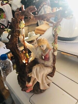 Ceramic figurine young couple lovers on tree swing