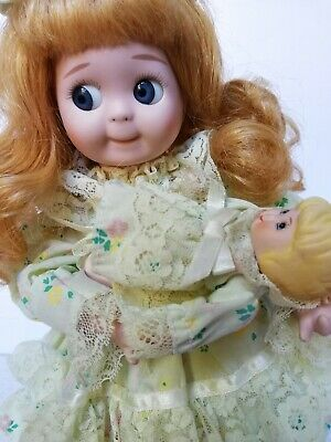 Musical, moving Googly eye porcelain doll 11 inch. Rocks her baby doll to music