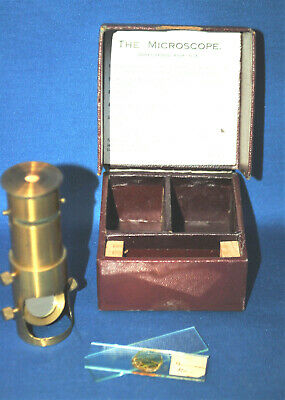 An antique Victorian brass pocket microscope, mirror base, box and slides, A/F