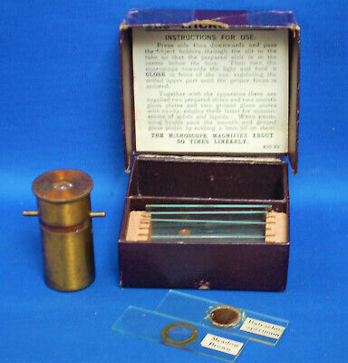An antique Victorian brass pocket microscope, with box and slides