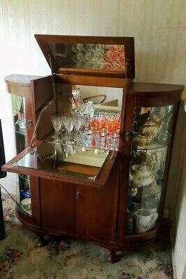Curved glass cocktail cabinet. Good condition. Mirrored surfaces inside.