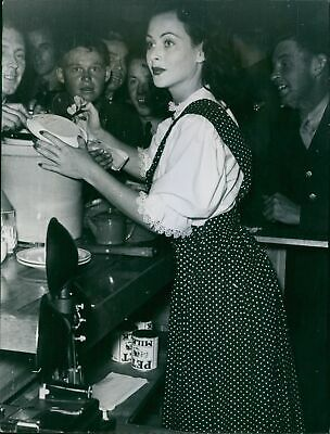 Hedy LaMarr behind the Canteen snack bar, autographs a paper plate for an admire