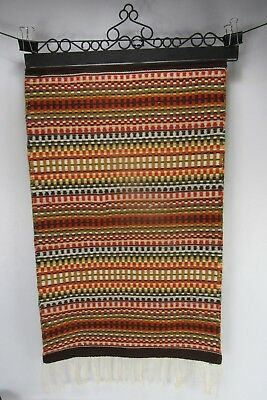 Beautiful Hand-woven Scandinavian decorative rug on wrought-iron hanger.