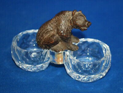 A well carved antique Victorian Black Forest sitting bear figure, glass dishes