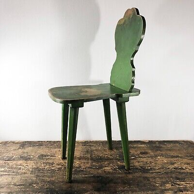 An antique peasant spinning chair in original green paint.