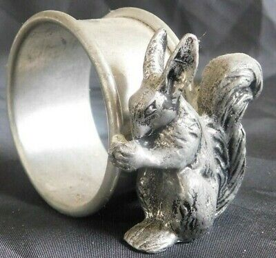 Pewter figural napkin ring of a squirrel eating a nut next to ring