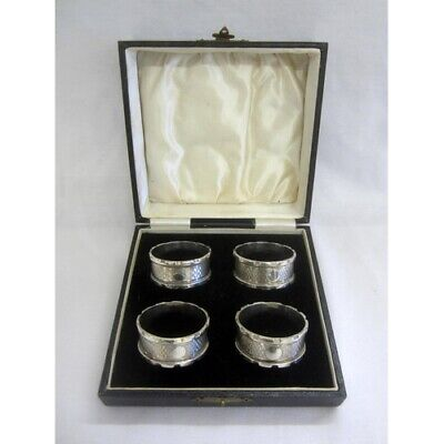 4 Silver Napkin Rings with vacant cartouches, castellated rims, engine turned bo