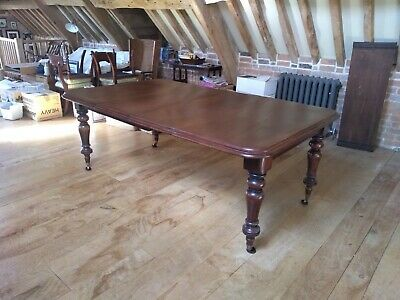 Antique Victorian Mahogany extending dining table, carved legs, castors.