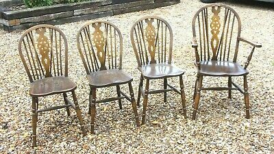 Set of four oak framed wheel backed dining chairs with one carver