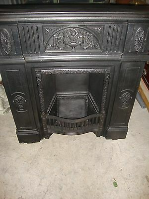 Large antique cast iron fireplace with top shelf