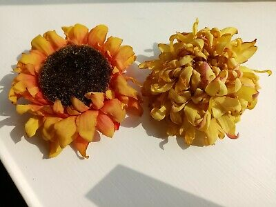 Two fabric flower fascinators, sunflower and dahlia, orange and gold tones