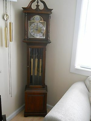 A vintage grate looking Grandfather clock made by Howard Miller-working..