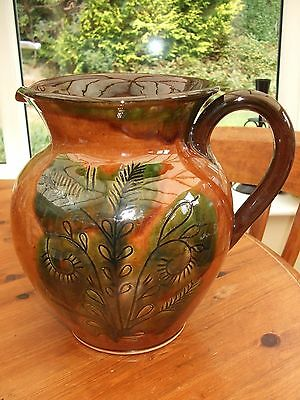 A Large Brown Glazed Pottery Jug Decorated With Green Foliage.
