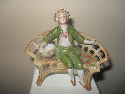 vintage glazed porcelain figure of a young man on a bench