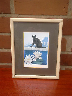 Black cat by a pond with waterlilies. Framed print.