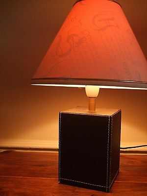 a brown faux leather based table lamp with matching cream shade.makers mark,s.h.