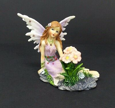 Fairy Figurine in Purple Dress with Glitter Accents Sitting Beside Pink Flowers