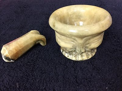 Vintage marble pestle and mortar with a face