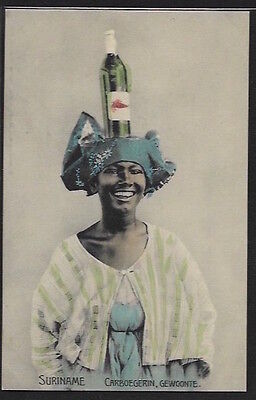 SURINAME - Carboegerin, Gewonte. Caribean woman carrying a bottle of White Wine.