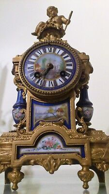 French Gilt Metal Figural Mantel Clock inset with Sevres Panels.