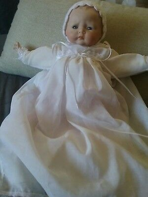 porcelain doll dressed in christening gown with booties and bonnet