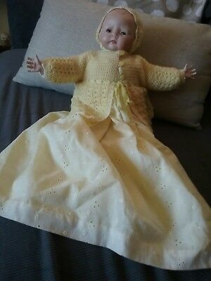 porcelain doll dressed in yellow christening gown, cardigan, bonnet and booties