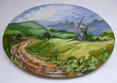 An Oil Painting Of A Windmill On An Oval Wooden Plaque