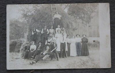 Vintage sepia postcard of a group of people with a large hay bale?