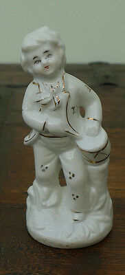 small porcelain figurine of boy playing the tambourine