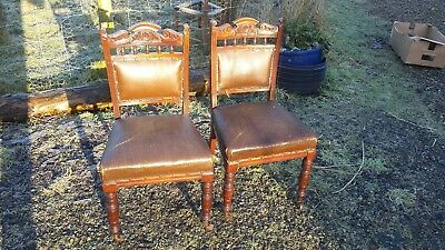 pair of edwardian leatherette chairs with front castors and sprung seats