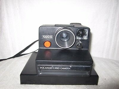 Vintage Polaroid 1000s SX70 type instant camera and flash
