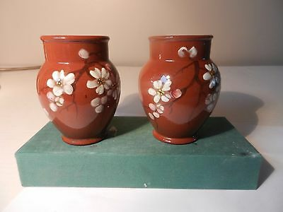 A matched pair of enamelled flowered Watcombe pottery vases