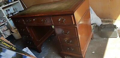 Antique wooden desk with locking drawers and a green leather top.
