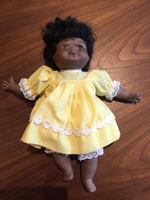 Small brown skin porcelain doll with yellow dress