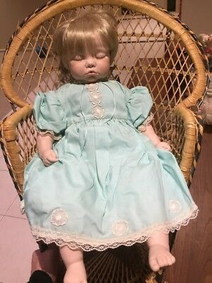 Porcelain sleeping baby in green dress